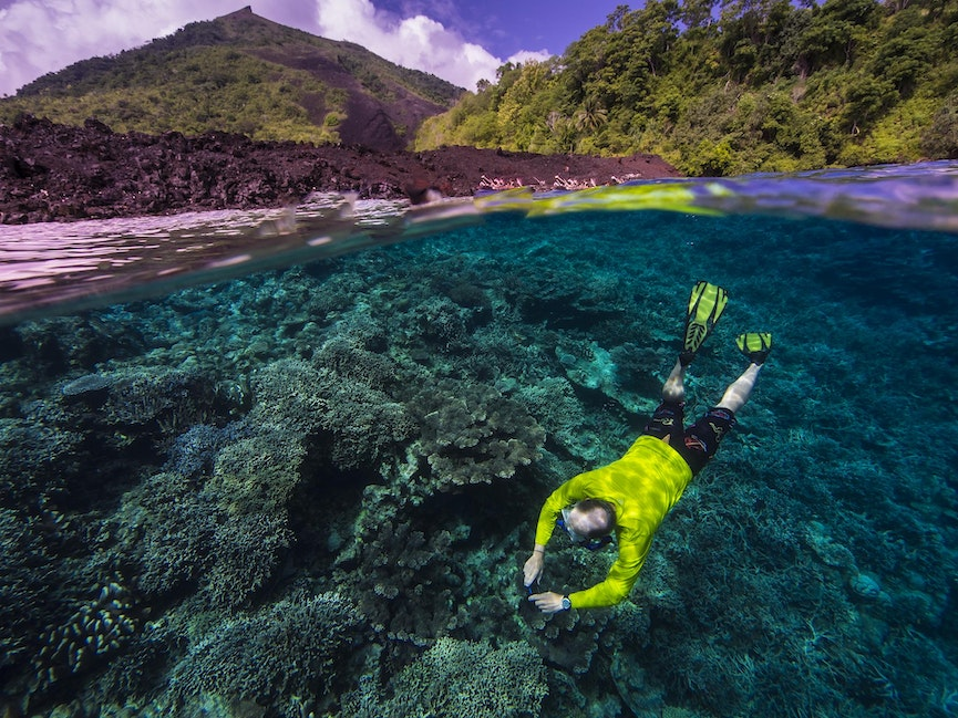 Free Diver Below Gunung Api Volcano - A 1988 lava flow cuts through the forest into the sea, where the coral reef has covered the bare rock